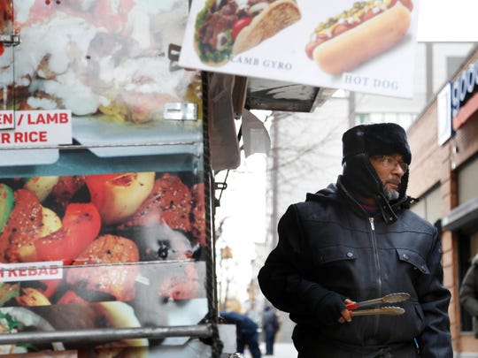 In this Nov. 21, 2016 photo, Mohammed Shaheedul Huq serves a customer from his food cart in the Brooklyn borough of New York. For decades, the city's regulatory scheme has made it next to impossible to obtain a new permit to operate a food cart or truck. Unable to get a permit of his own, Huq, paid $18,000 upfront to lease one from a man who pays the city just $200 every two years for the license.
