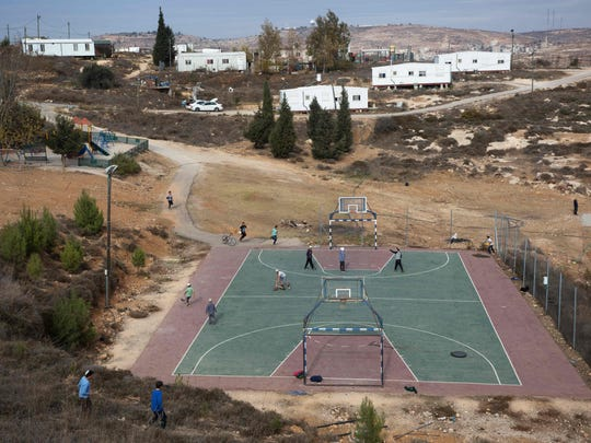 Israeli settlers play in the settlement outpost of