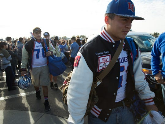 Damian Aguirre, heads the line of Las Cruces High School football players as they walked through a crowd of fellow students, teachers and parents that came out Friday, December 2, 2016, to Las Cruces High to send the team off to their state playoff game in Rio Rancho.