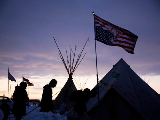 Travelers arrive at the Oceti Sakowin camp where people have gathered to protest the Dakota Access oil pipeline as they walk into a tent next to an upside-down american flag in Cannon Ball, N.D., Dec. 2, 2016.