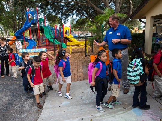 Executive Director Tim Ferguson, right, waves to kids as they file in for lunchtime at Grace Place for Children and Families in Naples on Monday, Dec. 5, 2016.