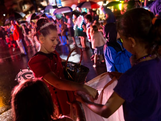 A girl passes out candy to kids during the Naples Christmas Parade at Third Street South on Tuesday, Dec. 6, 2016.