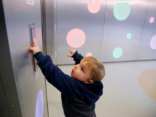 Abram Miller, 4, pushes the button to ride the elevator