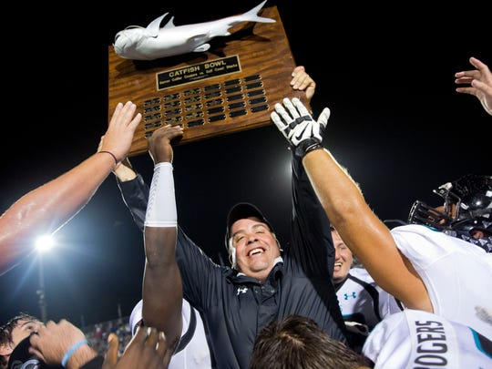 Gulf Coast Football Head Coach Pete Fominaya smiles as he hoists the Catfish Trophy after his team defeats Barron Collier High School Friday, October 7, 2016 in Naples. Gulf Coast would win 15-11 clinching their first Catfish Bowl since 2007.