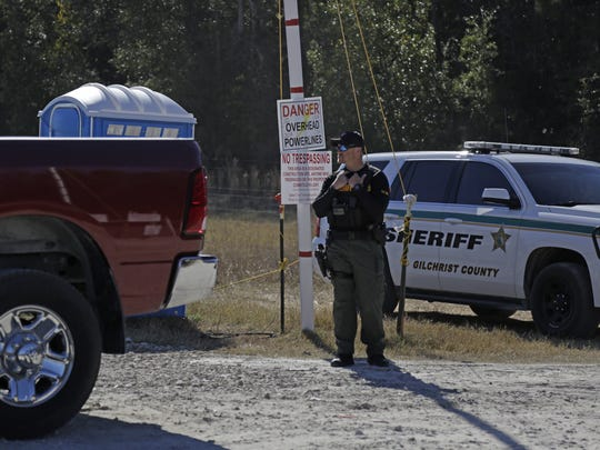 Off-duty Gilchrist County sheriff's deputies are posted at the construction site off 117th place on the Santa Fe River.