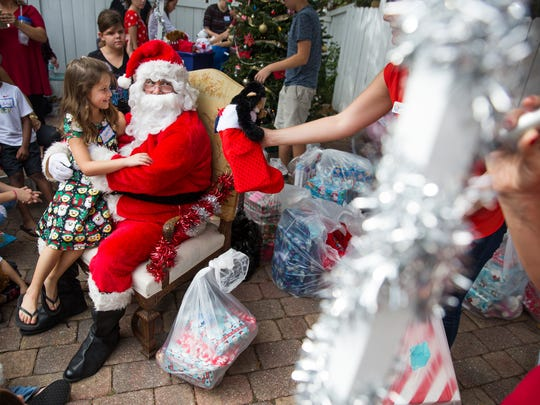 Sophia Consolo, 8, sits on Santa's lap and tells him
