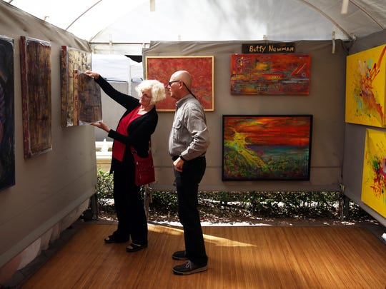 Artist Betty Newman of Marco Island shows Frank Fleischacker of Cedar Rapids, Iowa a piece of her art during the Left Bank Art Fest at the Esplanade Shoppes on Marco Island on Sunday, Feb. 28.