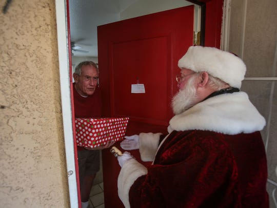 Fred Walker gets a present of a disaster preparedness kit from Bob Elias, the director of social services and Meals on Wheels for the Joslyn Center, dressed as Santa on Thursday, December 22, 2016 in Palm Desert. Every year Elias dons the Santa suit to visit homebound seniors who receive meals from Joslyn Center in Palm Desert.