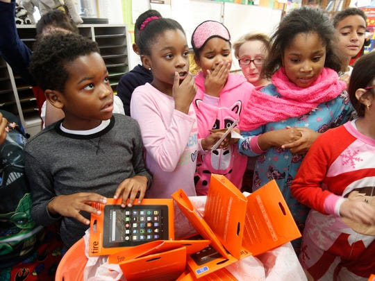Children look at the tablets donated to the fourth-grade