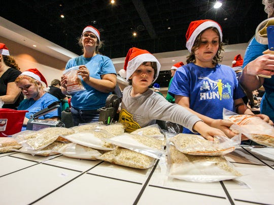 Volunteers pack food for the hungry during the 2016 Holidays Without Hunger event at Harborside Event Center in downtown Fort Myers.