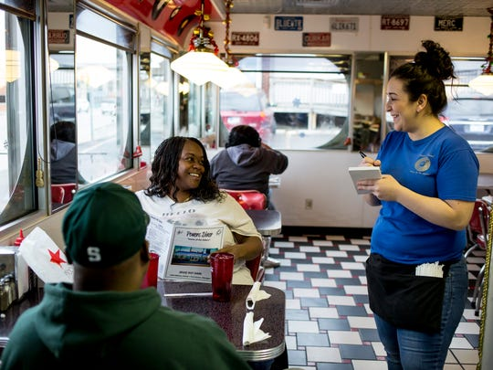 """Waitress Bianca Jackson takes an order from Persondra Howard, of Marysville, Thursday, Dec. 29, 2016 at Powers Diner in downtown Port Huron. In 2017, minimum wage will increase from $8.50 to $8.90, and for tipped workers the rate will rise from $3.23 to $3.38. """"It would have to go up a couple dollars at least for me to see a significant change,"""" Jackson said, who works 40 to 50 hours each week at three part-time jobs."""