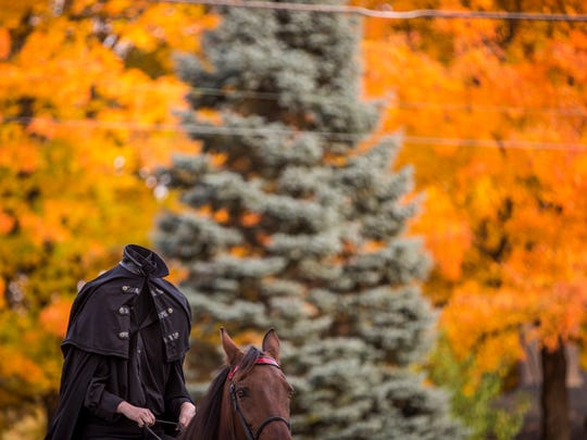 Megan Smith rides as the headless horseman on her own horse to entertain those in local neighborhoods for Halloween in 2016. Smith has been riding through the Cowing Park neighborhood for 16 years.