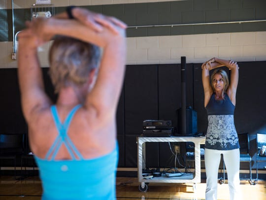 """Wendy Campbell, 41, right, leads a yoga class at the North Collier Regional Park gym on Friday, Dec. 16, 2016. Campbell, who was diagnosed with hodgkin's lymphona 10 years ago, is trying to bridge that gap between cancer treatment and mental well-being through her start-up organization called """"Survive & Thrive."""" Campbell teaches cancer survivor yoga and provides them with other wellness resources."""