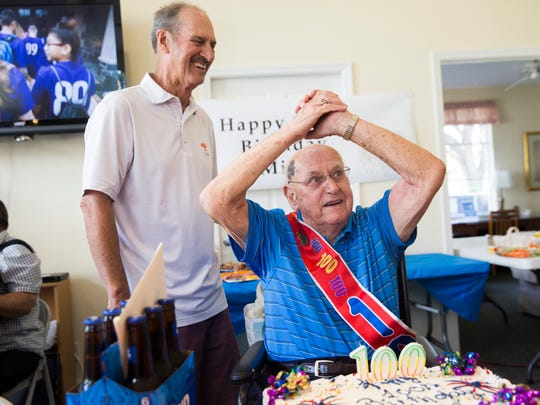 Michael Jordanek Jr., 100, celebrates with his son Ron, left, and a number of other family and friends shortly after blowing out his birthday candles at the clubhouse at Villages of Bonita on Sunday, Jan. 1, 2017. Jordanek was born on New Year's Day 1917.
