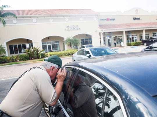 Collier County Sheriff's Office volunteer William Leach checks cars for visible valuables in the parking lot of Shoppes at Vanderbilt on Wednesday, Jan. 4, 2017. The burglary prevention initiative was conducted by the Collier County Sheriff's Office.