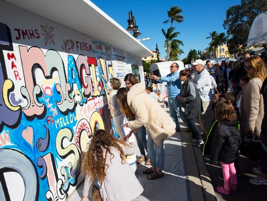 Members of the public paint a section of the mural
