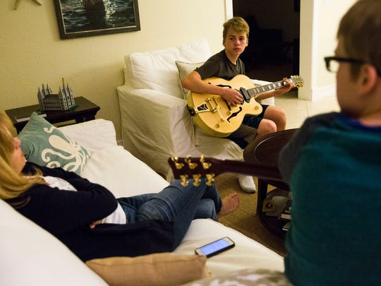 Annika Dean listens as her sons Austin, 13, center, and Brandon Foote, 11, practice guitar in their Parkland, Fla. home on Monday, January 9, 2017. Dean survived Friday's shooting at Fort Lauderdale-Hollywood International Airport.