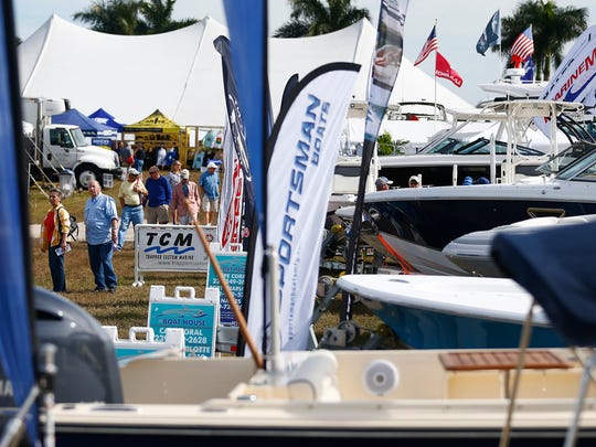 Patrons peruse boats Thursday, Jan. 21, 2016 at the Naples Municipal Airport during the 49th annual Naples Boat Show.
