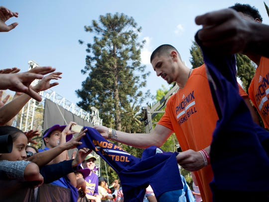 Phoenix Suns' Alex Len hands out T-shirts to gathered fans, along with teammate TJ Warren, obscured, in the NBA fan zone at Chapultepec Park, in Mexico City, Friday, Jan. 13, 2017. After losing to the Dallas Mavericks on Thursday, the Phoenix Suns will take on the San Antonio Spurs in Mexico City Arena on Saturday. Mexico is hosting two games in one regular season for the first time in NBA history.