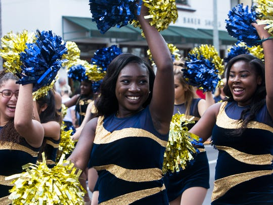 Members of the Naples High School color guard smile and cheer to the audience during the 20th Annual Rev. Dr. Martin Luther King Jr. Parade and Celebration in downtown Naples on Monday, Jan. 16, 2017.