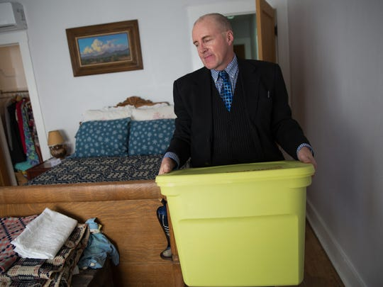 Bret Martin, designer and owner of BL Martin and Associates, carries a box into a room in Jane Grider home where he has recently helped Grider reorganize and design her home, Wednesday January 18, 2017.