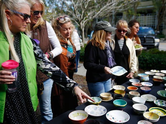 Teresa Simpson, left, points out bowls to her sister, Donna Larson, both of Naples, Saturday, Jan. 23, 2016 at Cambier Park in Naples, Fla.