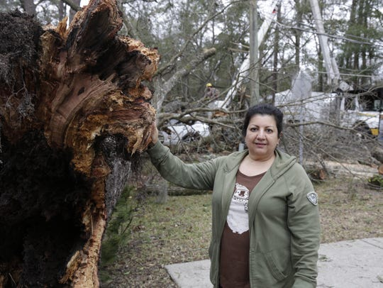 Marita Cueras stands by the base of a tree that fell