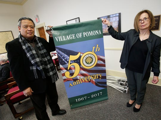Tjokorda Gde Arsa Artha, director of the Village of Pomona Cultural Center, and Village Clerk Fran Arsa Artha hold one of several village 50th anniverary banners, Jan. 23, 2017.
