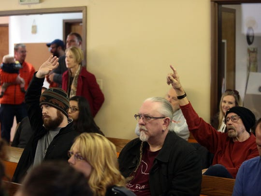 Forest Falls residents John O'Neill, left, and Jerry Jacobs raise their hands to ask questions about a proposal to sell water for bottling during a town hall meeting on Jan. 14 at Valley of the Falls Community Church.