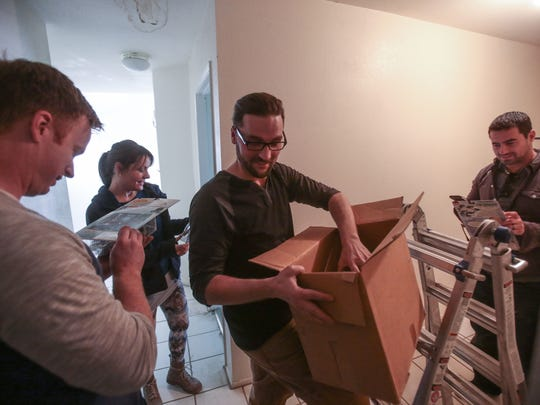 'Desert Flippers' host Eric and Lindsey Bennett, left, co-host Mike Schneider and supervising producer Brian Seidel, right, fine a box of toys in their project house for season 2 of the HGTV show on Thursday, January 26, 2017 in Cathedral City.