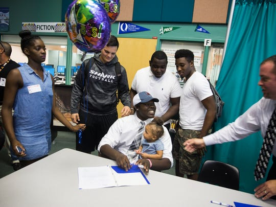 Jadavian Leccima takes photos with friends and family after signing to play football with Northwestern Oklahoma State University during National Signing Day at Gulf Coast High School on Wednesday, February 1, 2017 in North Naples. Six students from Gulf Coast High School signed to six different universities to play soccer and football.