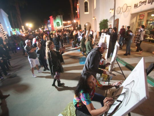 Hundreds of people filled Old Town La Quinta for the city's second annual 19th Hole Block Party. The event had something for all ages -- food, music, art and crafts -- under slightly chilly but clear skies. This year the city partnered with Coachella Valley Art Scene, a local nonprofit organization for artists of all media, which brought together local DJs, musicians and artists. Some artists battled to see who could create the most popular piece as voted on by event-goers. Local restaurants offered a variety of food and drinks to visitors. In this photo Clarissa Cervantes of Coachella Valley Art Scene draws with 14 other artist of the same organization.