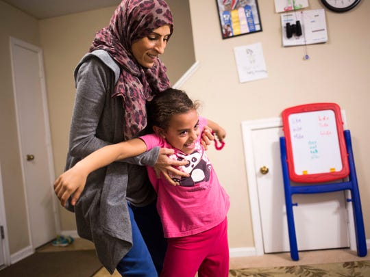 Mufida Ammar plays with her daughter Mariam Shukri, 6, including carrying her around their living room, on Thursday, February 2, 2017 in Clemson.