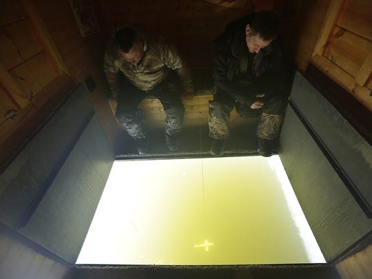 Lonny Ziemer of Rod-Bender Guide Service in Kaukauna and Paul Lueck of Fond du Lac take a peek at the ice hole they carved Thursday on Lake Winnebago near Oshkosh in preparation for Saturday's sturgeon spearing opener.