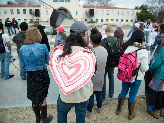 Sammy Joe Luna wears a paper heart in solidarity with the many different types of people and groups that joined together to march down the International Mall on the campus of New Mexico State University, Tuesday, February 14, 2017, protesting the Trump administration policies.