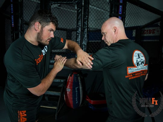 """Anthony Zettel, left, credits mixed martial arts training with Bruce Lombard, right, as helping him get to the NFL. He believes so much in it he helped Lombard produce an instructional video about """"hand-fighting."""""""
