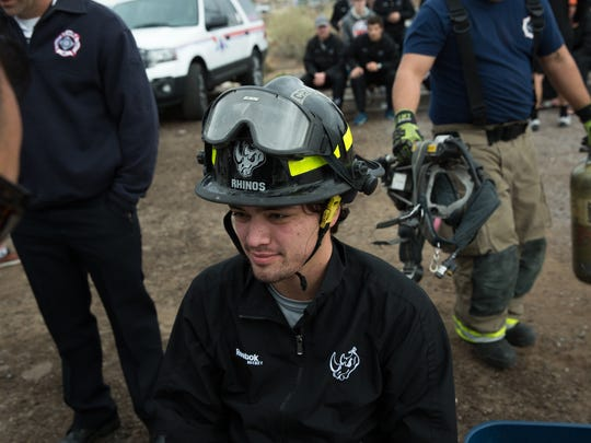 Evan Camba, a forward with the El Paso Rhinos Hockey team, suits up in fire fighting gear before taking on the training course at the Las Cruces Fire Department's training facility, Saturday, February 18, 2017