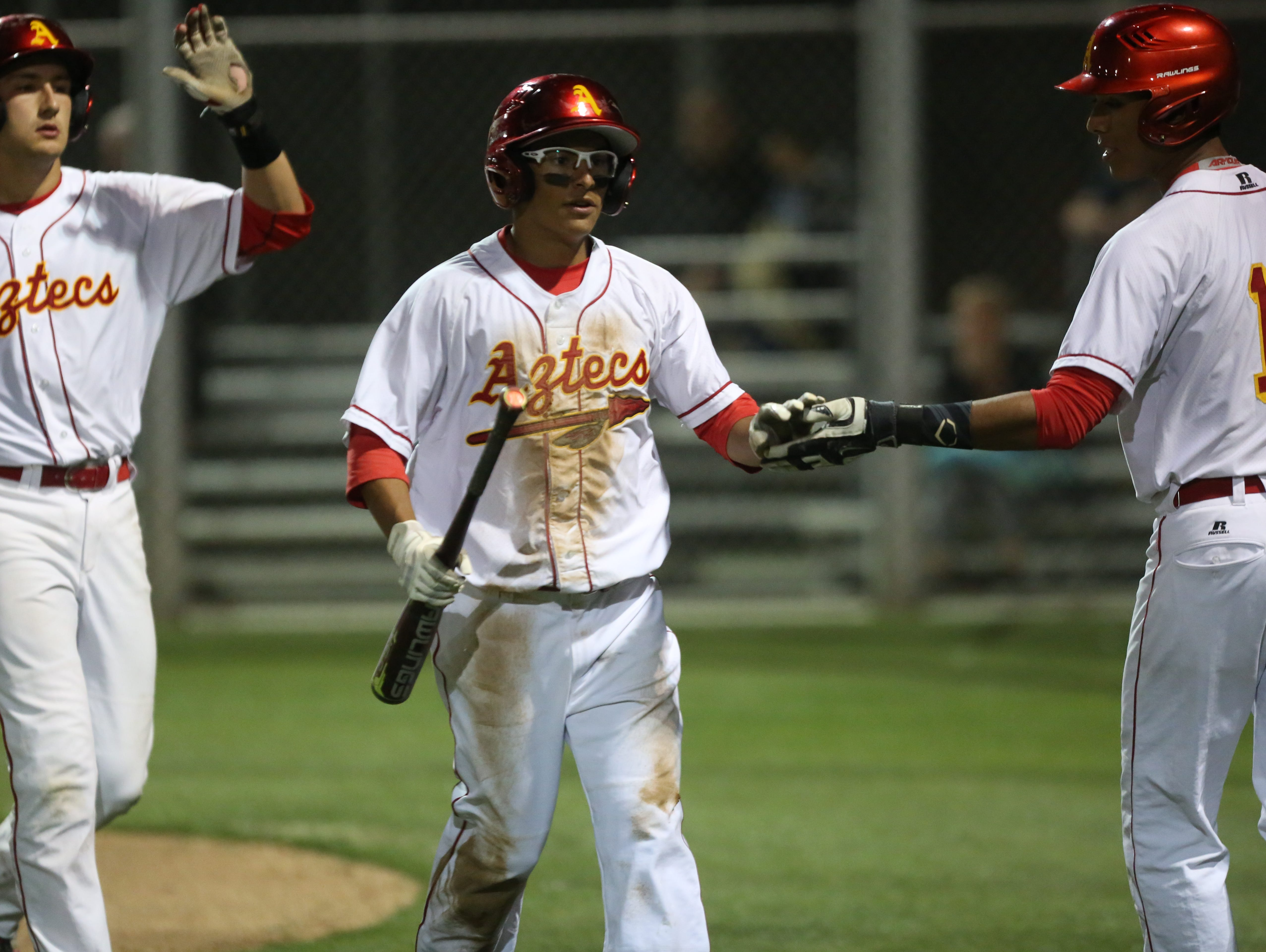 At far right, Palm Desert High School's Jeremiah Estrada congratulates Josh Hernandez after a scored run during their game against Foothill High School in Palm Desert on March 3, 2017.