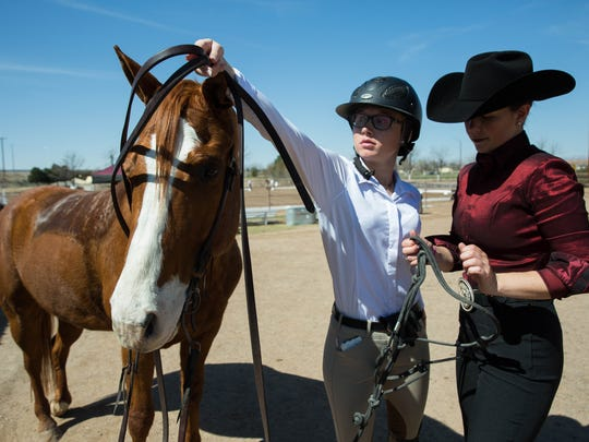 """Erin Gordon,left and Katlynn Crine, right, unbridle """"Blaze"""" one of the NMSU Equestrian teams horses after Katlynn Crine rode Blaze in the horsemanship portion of their final meet at NMSU. Saturday, March 4, 2017. The final meet was against Oklahoma State University, the final score was OSU 10, NMSU 5."""