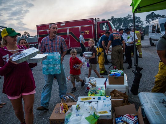 Families donate food for the emergency workers at the staging area in a parking lot on the corner of Collier Blvd and Davis Blvd on Tuesday, March 7, 2017. Community members and organizations donated food and drink to the workers.