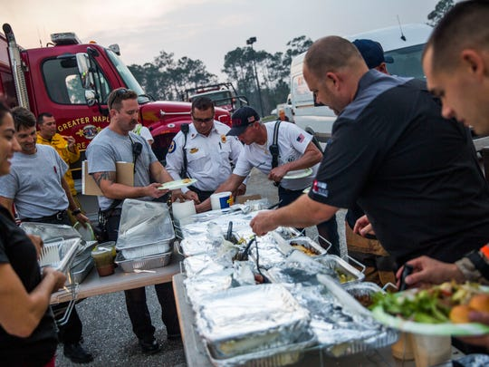 Emergency workers eat dinner during a break from fighting the Collier County brush fires at the staging area in a parking lot on the corner of Collier Blvd and Davis Blvd on Tuesday, March 7, 2017. Community members and organizations donated food and drink to the workers.
