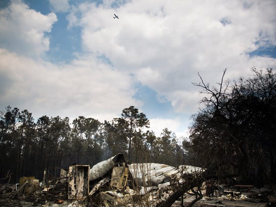 A home on Le Buffs Road continues to smoke on Wednesday, March 8, 2017, after it was destroyed by the Collier County brush fire .