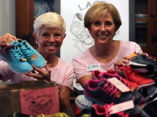 Susy Warren and Jeanne Nealon, co-founders of Laces of Love, show off donated new sneakers stored inside Nealon's Naples home on March 8, 2017. Every year, the nonprofit collects and delivers donated new sneakers to children in need in Collier and Lee counties.