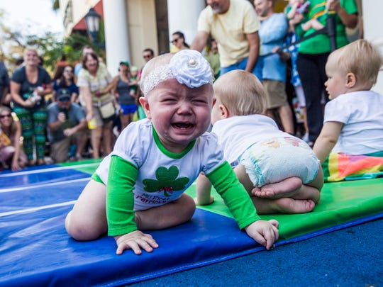 Scarlette Roling, 8 months old, of Bonita Springs begins to cry while racing in the leprechaun races at Miromar Outlets in Estero on Sunday, March 12, 2017.