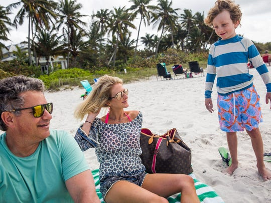 Evan and Heather Ardente of Providence, R.I., and son Blake, 9, spend time on the beach near the Naples Pier on Tuesday, March 14, 2017. Back home Tuesday, Providence had rain turning to snow and a wind chill of 21 degrees.
