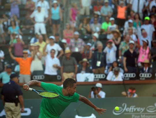 Nick Kyrgios, of Australia, hits autographed tennis