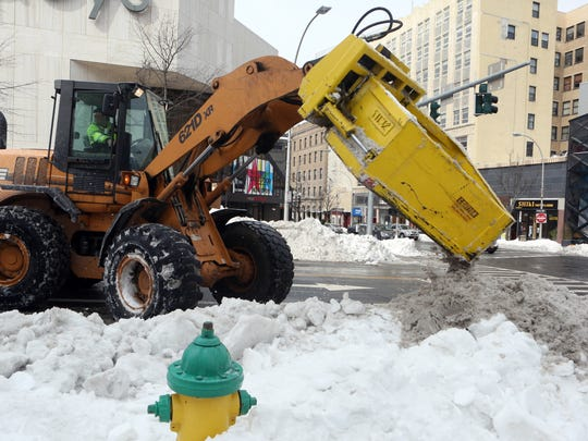 A worker from the Department of Public Works clears snow from a crosswalk in downtown White Plains Wednesday.
