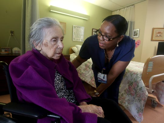 Nadeem Simpson, a licensed practical nurse at the Wartburg Home in Mount Vernon, cares for resident Anais Mueller March 16, 2017.