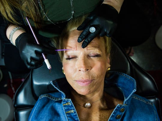 Alicia Shapira of Vintage Lashes Eyelash Extension Studio in Naples applies permanent eyebrows on to client Jeanne Mosher of Naples on Friday, March 17, 2017.