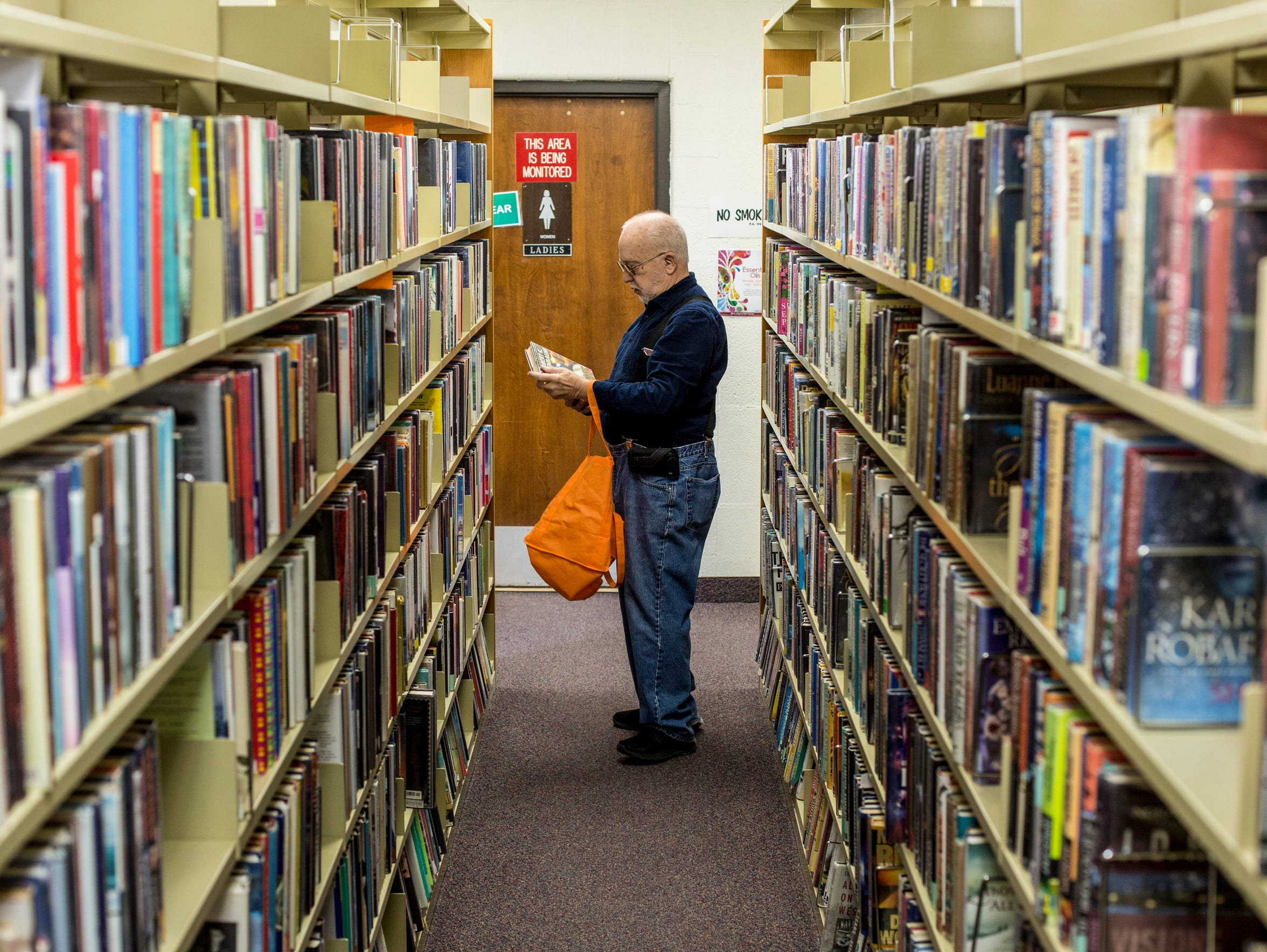 Gary Wickmiller, of Port Huron, looks over books Saturday,